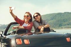 Deux amis féminins prennent une photo de selfie dans la voiture de cabriolrt pendant le t Image libre de droits