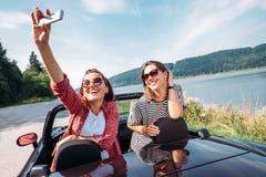 Deux amis féminins prennent une photo de selfie pendant leur voyage automatique Photos libres de droits