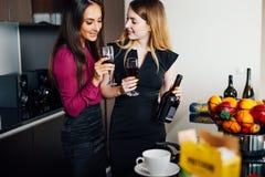 Deux amis féminins rattrapant tout en buvant du vin à la maison Photographie stock