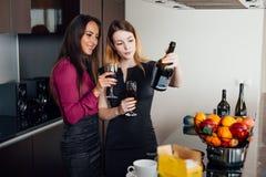 Deux amis féminins rattrapant tout en buvant du vin à la maison Image stock
