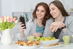 Deux amis féminins regardant le smartphone Photo stock