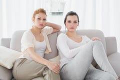 Deux amis féminins sérieux s'asseyant sur le sofa dans le salon Photos libres de droits