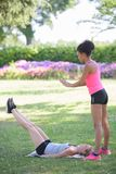 Deux amis féminins s'étirant au parc après avoir pulsé Image libre de droits