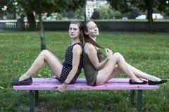 Deux amis féminins s'asseyant de nouveau au dos sur un banc de parc Images libres de droits