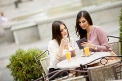 Deux amis féminins s'asseyant dehors dans un café et ont l'amusement Photo stock