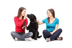 Deux amis féminins s'asseyant et jouant avec un chien Image libre de droits