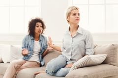 Deux amis féminins s'asseyant sur le sofa et l'argumentation Photo stock