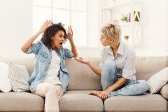 Deux amis féminins s'asseyant sur le sofa et l'argumentation Photos stock