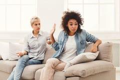 Deux amis féminins s'asseyant sur le sofa et l'argumentation Photographie stock