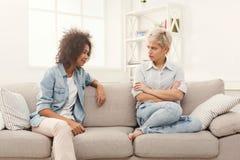 Deux amis féminins s'asseyant sur le sofa et l'argumentation Images libres de droits