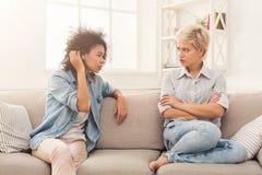 Deux amis féminins s'asseyant sur le sofa et l'argumentation Image stock