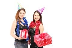 Deux amis féminins se tenant étroits ensemble et tenant des cadeaux à Images stock