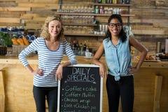 Deux amis féminins se tenant avec l'enseigne de menu au compteur Photo libre de droits