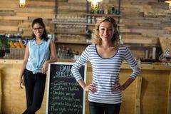 Deux amis féminins se tenant avec l'enseigne de menu près du compteur Images libres de droits