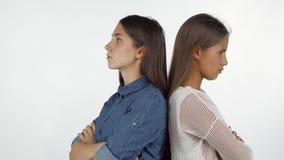 Deux amis féminins se tenant de nouveau au dos semblant fâché après avoir eu un combat photo stock