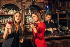 Deux amis féminins sont dans la barre pour une boisson et parlent La femme avec des entretiens près de l'oreille de l'ami Photographie stock libre de droits