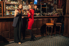 Deux amis féminins sont dans la barre pour une boisson et parlent La femme avec des entretiens près de l'oreille de l'ami Image libre de droits