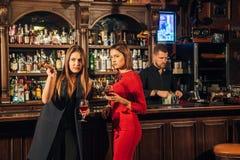 Deux amis féminins sont dans la barre pour une boisson et parlent La femme avec des entretiens près de l'oreille de l'ami Image stock