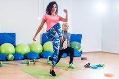Deux amis féminins sportifs établissant dans un gymnase faisant le genou- inverse de mouvement brusque s'exercent Photographie stock libre de droits