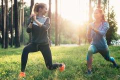 Deux amis féminins sportifs utilisant des salopettes faisant des mouvements brusques s'exerçant ensemble dehors Photo libre de droits