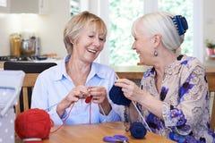 Deux amis féminins supérieurs tricotant à la maison ensemble Photo libre de droits