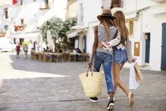 Deux amis féminins sur des achats de vacances dans Ibiza, vue arrière Photos libres de droits