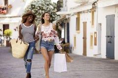 Deux amis féminins sur des achats de vacances dans Ibiza, vue de face Images libres de droits