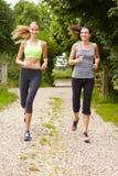 Deux amis féminins sur la course dans la campagne ensemble Image stock