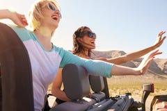 Deux amis féminins sur le voyage par la route derrière la voiture convertible Images libres de droits