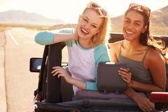 Deux amis féminins sur le voyage par la route derrière la voiture convertible Photo stock