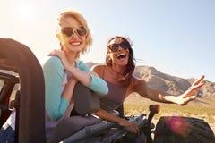 Deux amis féminins sur le voyage par la route derrière la voiture convertible Photographie stock