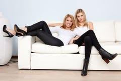 Deux amis féminins sur un sofa Photographie stock