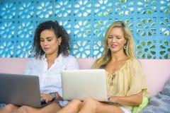 Deux amis féminins travaillant ensemble dehors au café frais avec l'ordinateur portable, une Caucasienne de fille, l'autre mélang Photographie stock