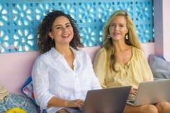 Deux amis féminins travaillant ensemble dehors au café frais avec l'ordinateur portable, une Caucasienne de fille, l'autre mélang Photos stock