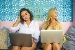 Deux amis féminins travaillant ensemble dehors au café frais avec l'ordinateur portable, une Caucasienne de fille, l'autre mélang Photographie stock libre de droits