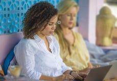 Deux amis féminins travaillant ensemble dehors au café frais avec l'ordinateur portable, une Caucasienne de fille, l'autre mélang Image libre de droits