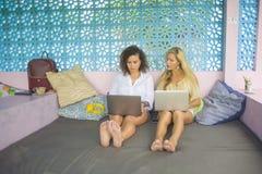 Deux amis féminins travaillant ensemble dehors au café frais avec l'ordinateur portable, une Caucasienne de fille, l'autre mélang Image stock