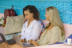 Deux amis féminins travaillant ensemble dehors au café frais avec l'ordinateur portable, une Caucasienne de fille, l'autre mélang Photo libre de droits