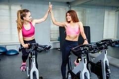 Deux amis féminins utilisant des vêtements de sport donnant la haute cinq tandis que cardio- séance d'entraînement dans le gymnas Photo stock