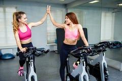 Deux amis féminins utilisant des vêtements de sport donnant la haute cinq tandis que cardio- séance d'entraînement dans le gymnas Image libre de droits
