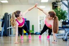 Deux amis féminins utilisant des vêtements de sport donnant la haute cinq tout en s'exerçant sur le plancher dans le gymnase Photographie stock