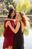 Deux amis f?minins dansent heureusement dehors le long des rivages d'un lac photos libres de droits