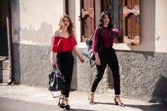 Deux amis f?minins marchent le long de la rue photo stock