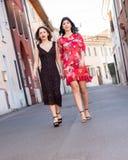 Deux amis f?minins marchent le long de la rue photographie stock