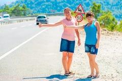 Deux amis faisant de l'auto-stop l'été Photo stock