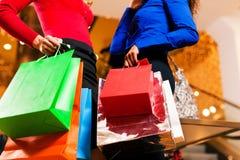 Deux amis faisant des emplettes dans le mail avec des sacs Images stock