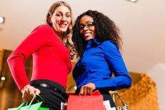 Deux amis faisant des emplettes dans le mail avec des sacs Photos stock