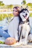 Deux amis fille et chien se repose près du lac Photos libres de droits