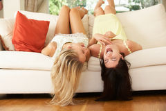 Deux amis féminins se trouvant upside-down sur le sofa Photos libres de droits