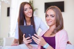Deux amis gais ayant l'amusement et regardant le PC mobile de comprimé Images stock